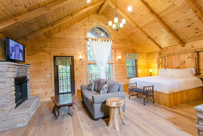 Lofty Willows Tree House bed and seating area with fireplace