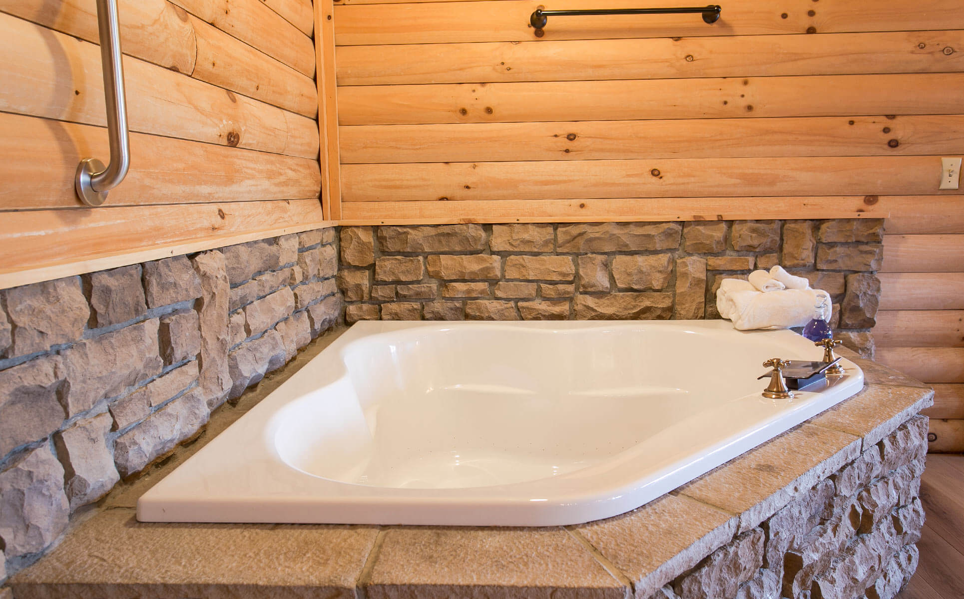 Two-person soaking tub surrounded by stone