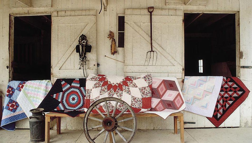 Amish Quilts in front of a barn with wagon wheel