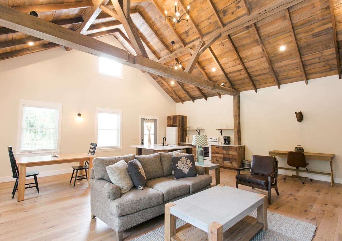 Interior of Barn Suite with couch, chair, desk, kitchen, and dining table