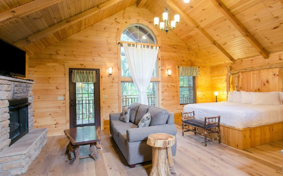 Interior of Tree House with bed, couch, stone fireplace, and TV