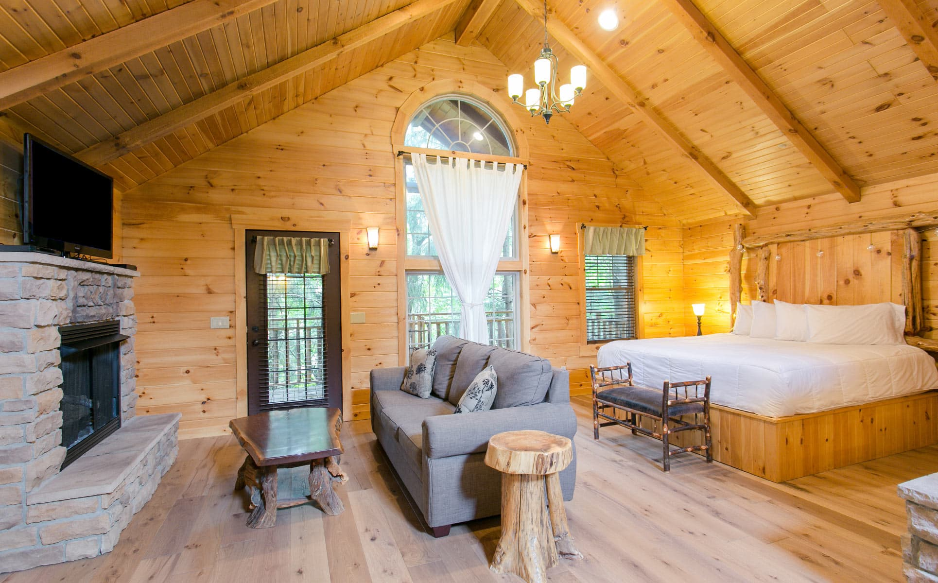 Interior of Treehouse with bed, couch, stone fireplace, and TV