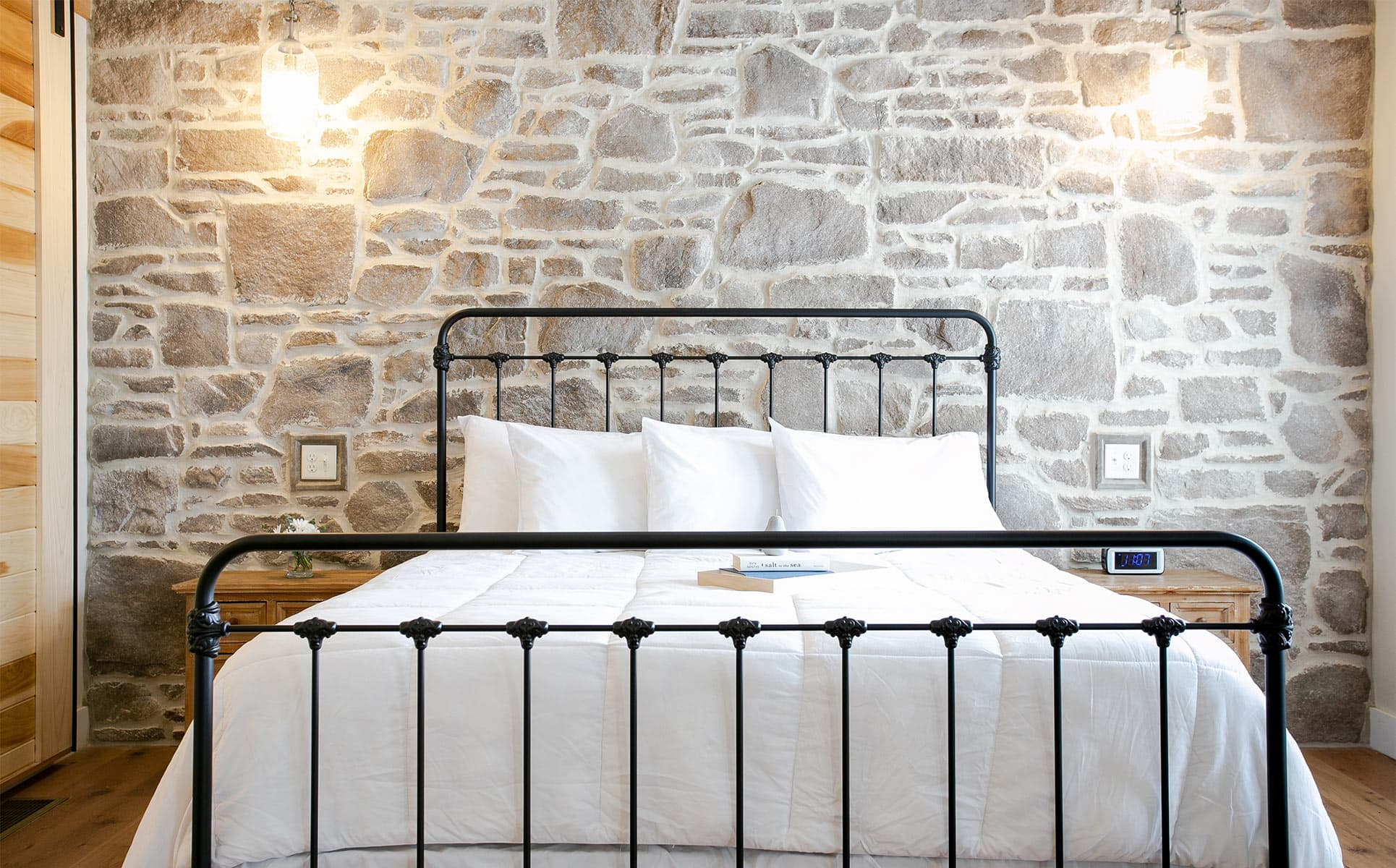 King bed against stone wall