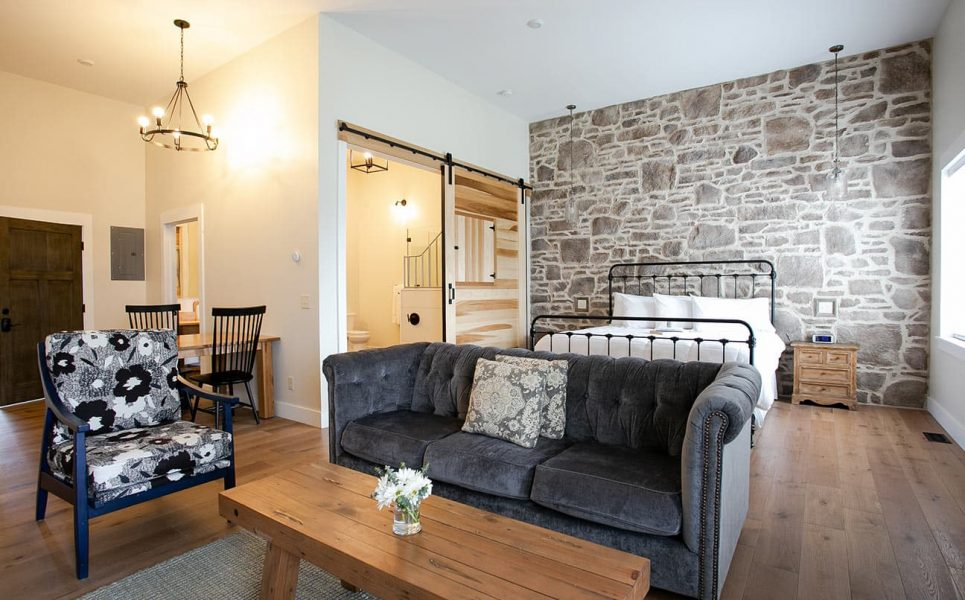 Magnolia Suite with couch, chair, and bed on stone wall