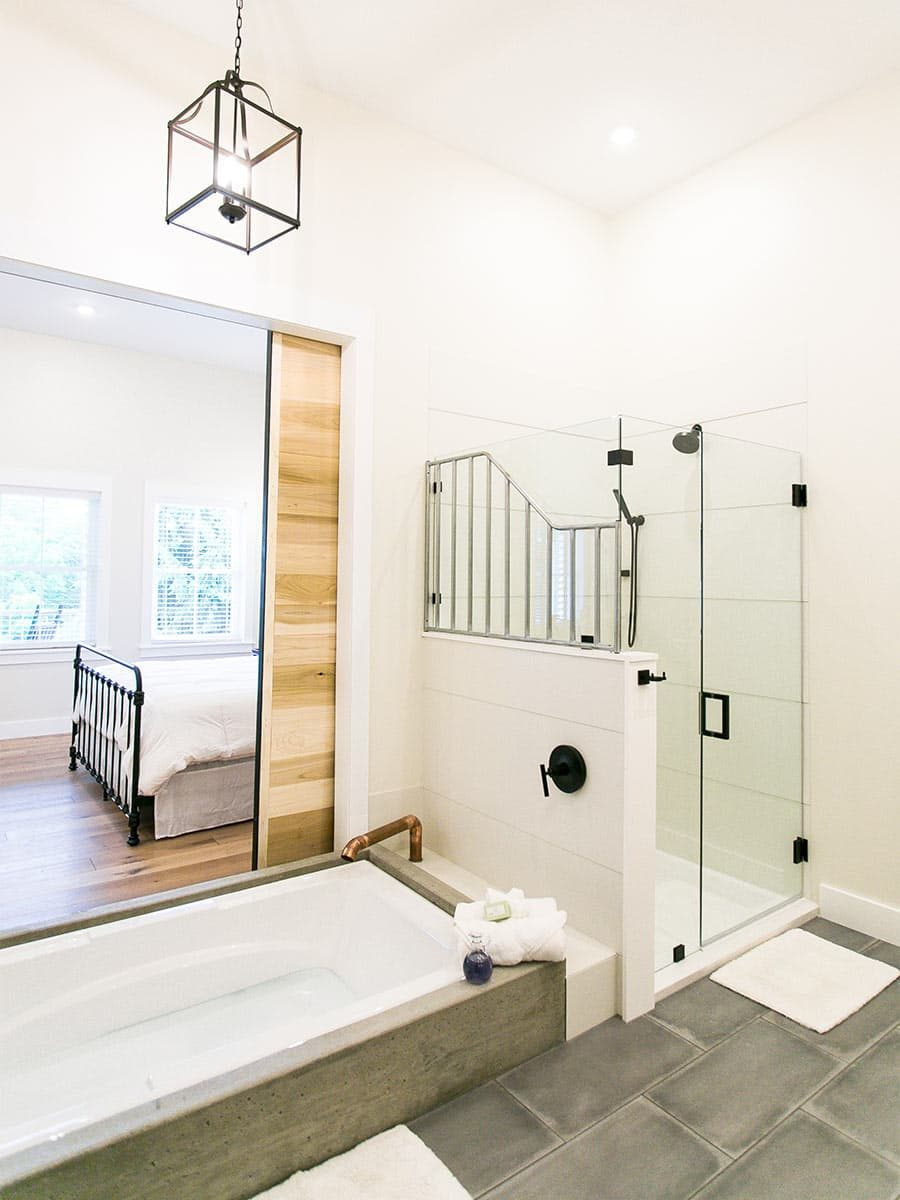 bathtub with barn door and walk-in shower