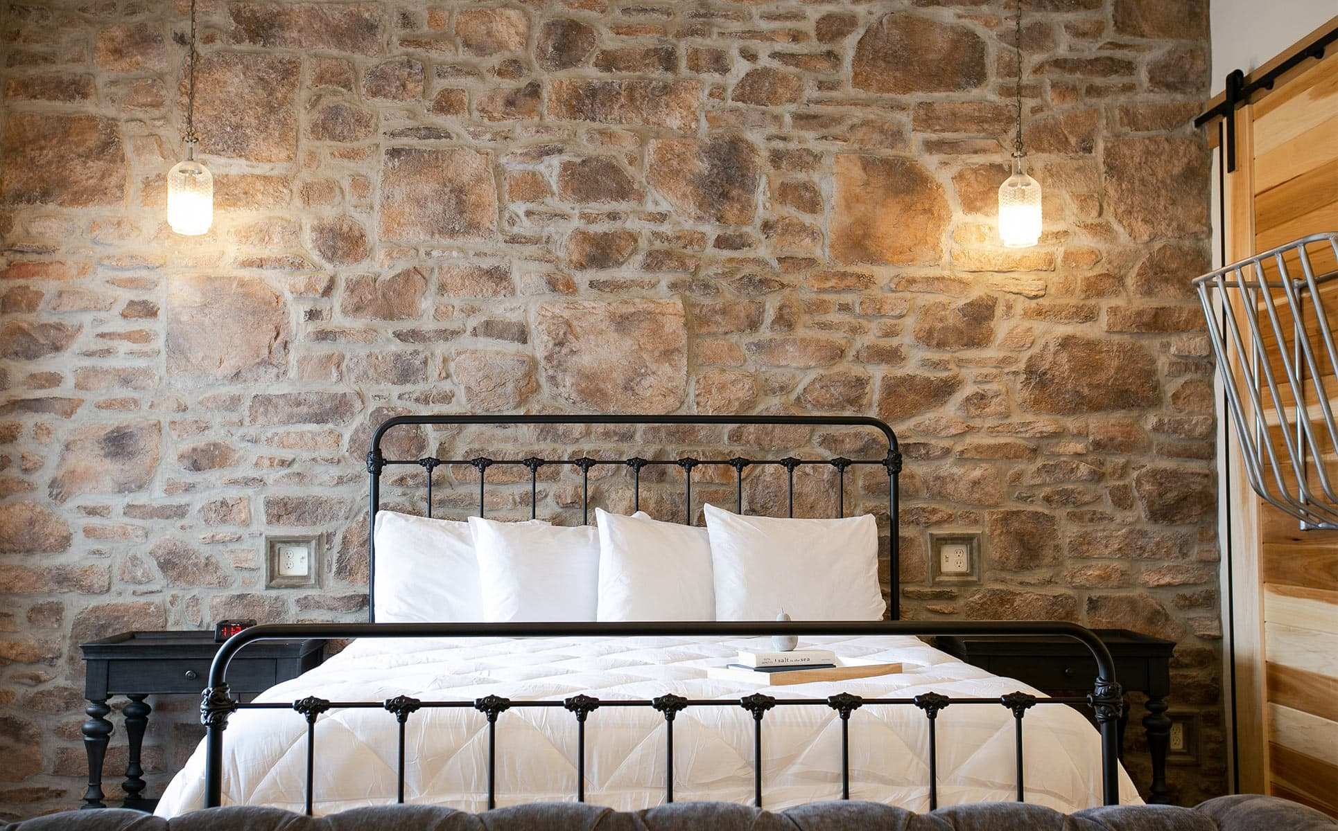 King bed in front of stone wall with pendant lights