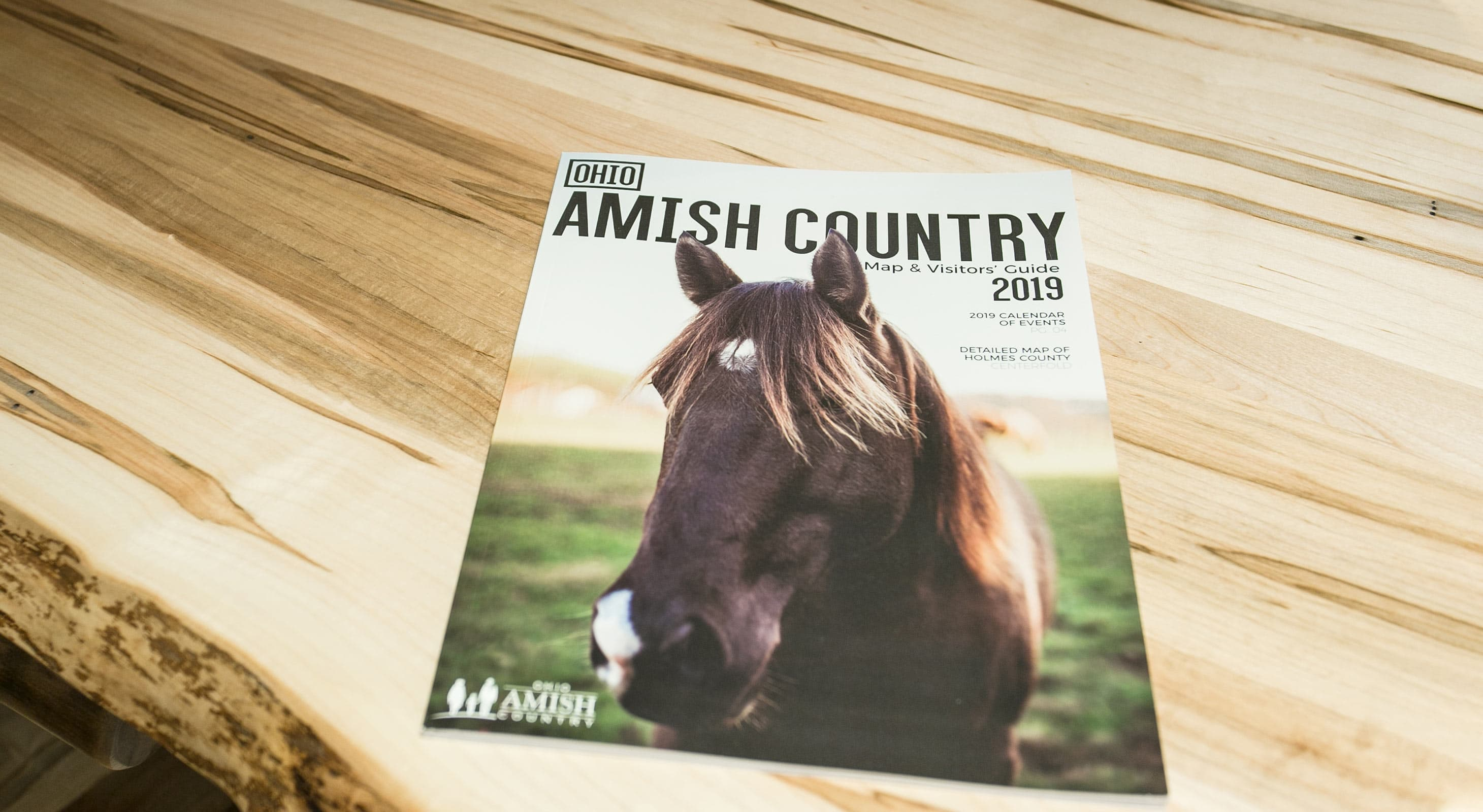 Cover of Ohio Amish Country Map & Visitors Guide 2019 - sitting on wood table