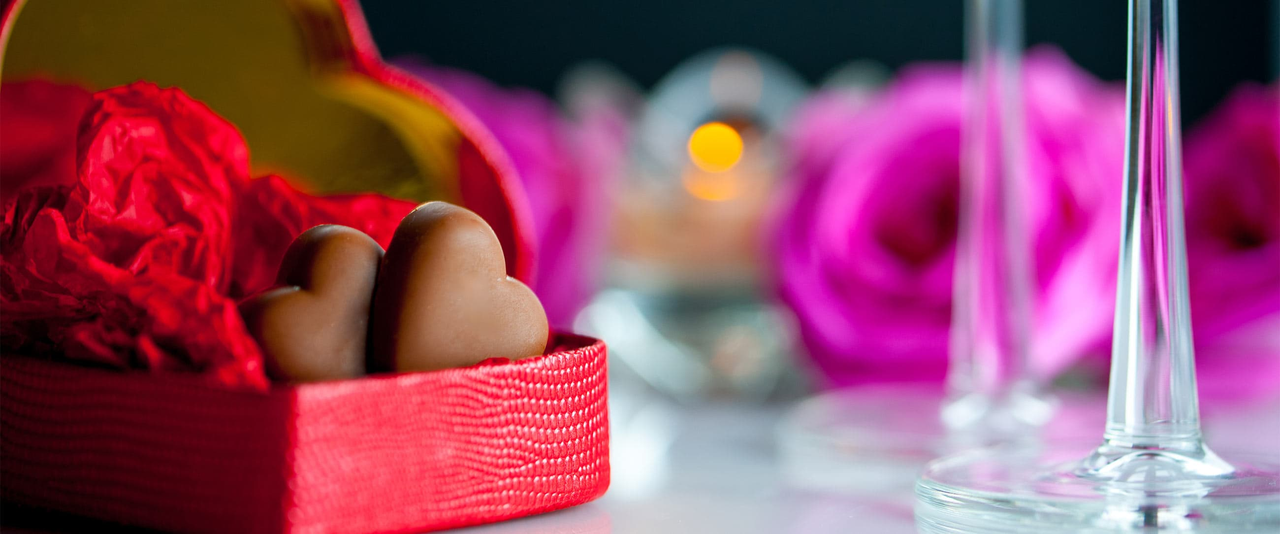 Chocolates in a red heart box with wine glass stems in background