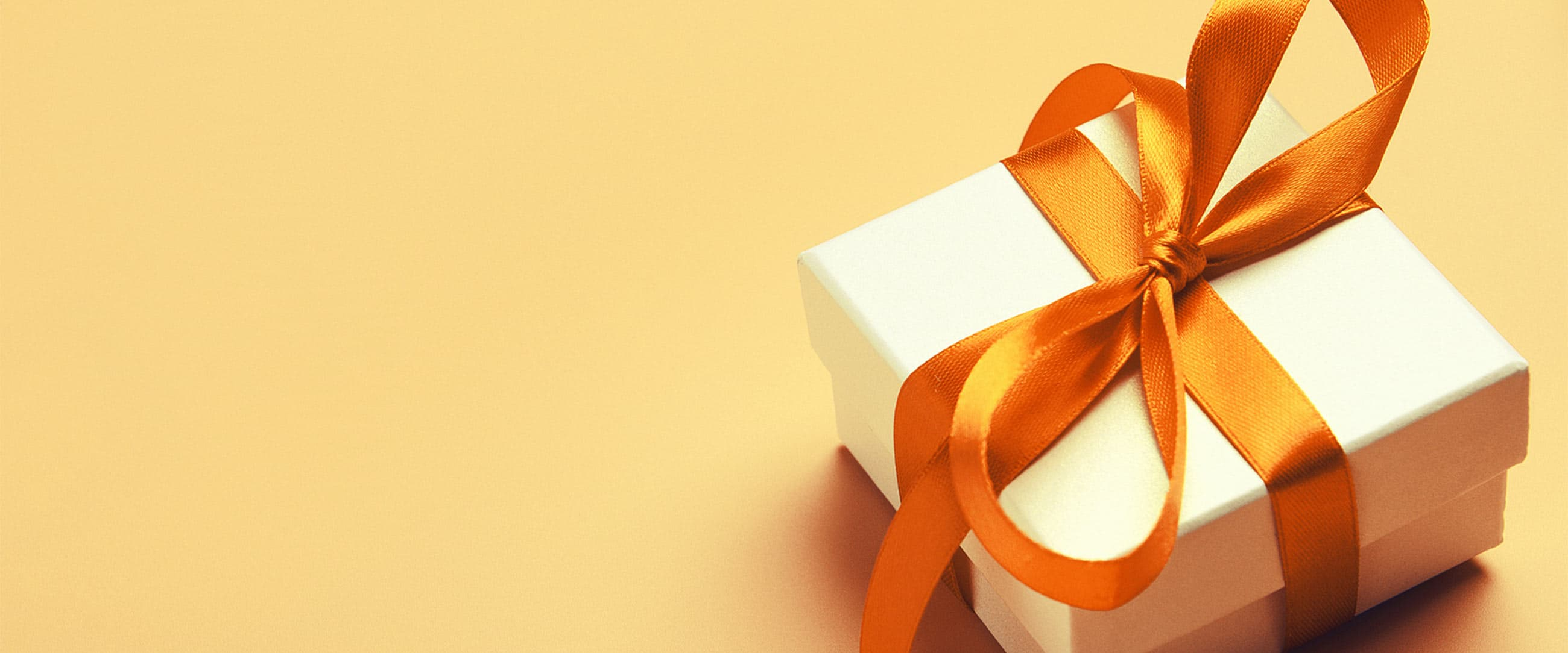 Gift Box with an orange bow on a yellow background