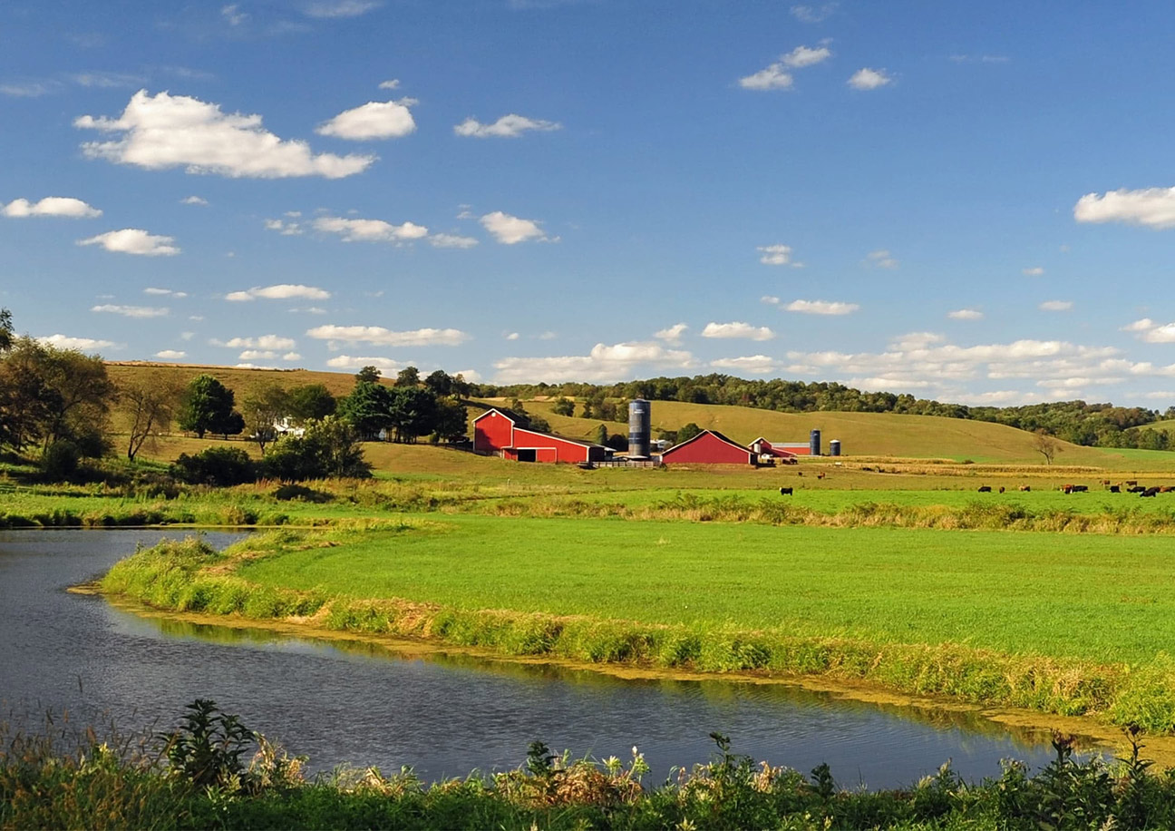 red barn in a field by a river
