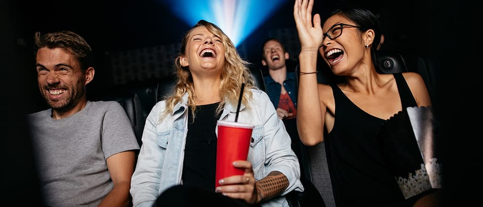 Friends watching a show in a theater and laughing